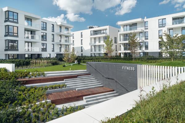 Budynki osiedla otoczone są nowo nasadzoną zielenią.
