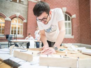 Studenci kombinują, jak zrobić wytrzymały most z papieru.