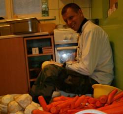 Wolontariusz czyści marchew na zupę wegańską.