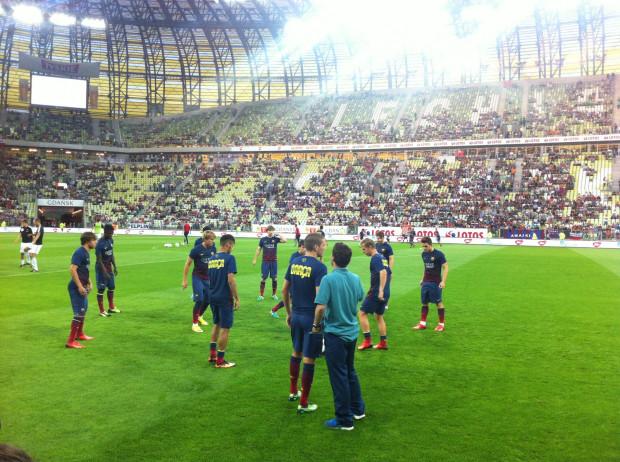 Piłkarze Bacy oglądający murawę i trybuny.