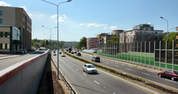 Trasa Słowackiego zajęła m.in. teren, gdzie wcześniej istniała ulica Partyzantów i taką też ulicę w adresie posiadają budynki widoczne na zdjęciu.