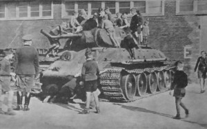"""Oblegany przez dzieci i młodzież niemiecką wrak sowieckiego czołgu T-34. Zdjęcie pochodzi z czasopisma """"Soldat im Weichselland"""" z 1943 r."""