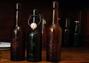 """Butelki z browaru Richarda Fischera z Gdańska Nowego Portu. Najbardziej popularna, zielona, przez kolekcjonerów nazywana jest """"butelką z ludzikiem""""."""