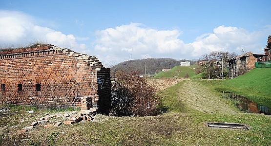 Zdewastowany mur leży w sąsiedztwie Bramy Nizinnej - widoczna w głębi, po prawej stronie zdjęcia.
