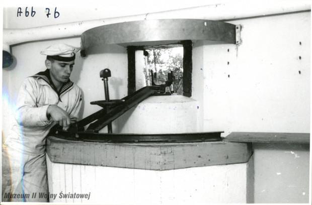 Niemiecki marynarz przy jednej z podstaw fortecznych dla (na zdjęciu zdemontowanego) ciężkiego karabinu maszynowego, prawdopodobnie w kabinie bojowej Wartowni nr 1.