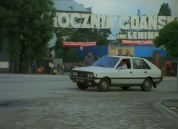 """Borewicz i Zubek zajeżdżają przed Stocznię Gdańską. W odcinku pt. """"Strzał na dancingu"""" cenzura wycięła Pomnik Poległych Stoczniowców, który znajdował się w szerszym kadrze."""