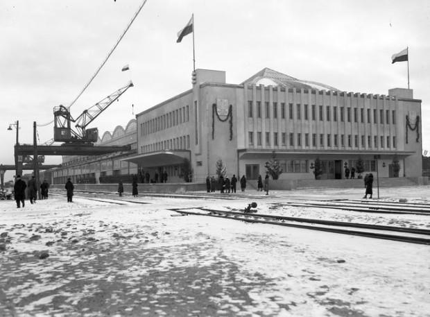 Widok zewnętrzny budynku Dworca Morskiego. Na ścianie dworca - płaskorzeźba stylizowanego orła. Widoczne urządzenia przeładunkowe. Zdjęcie wykonane w 1933 r.