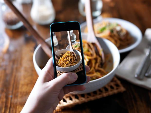 Ludzie siedzą razem przy stolikach, ale zamiast rozmawiać na żywo, wrzucają zdjęcia do portali społecznościowych i wymieniają się komentarzami, każdy wgapiony w swój telefon.