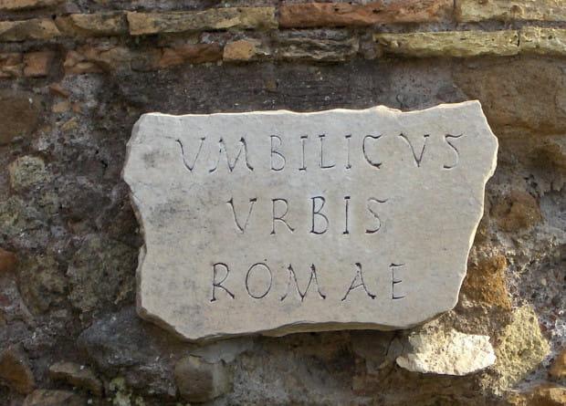 """Kamień wyznaczający środek starożytnego Rzymu. Łaciński napis """"Umbilicus Urbis Romae"""" oznacza dosłownie """"Pępek miasta Rzymu""""."""