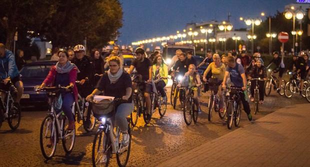 Nocny przejazd rowerowy skupia rowerzystów w różnym wieku.