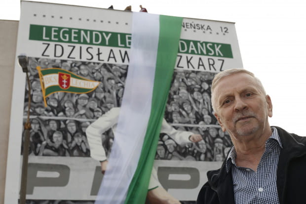 Zdzisław Puszkarz na tle muralu przy ul. Warneńskiej 12 w Gdańsku.