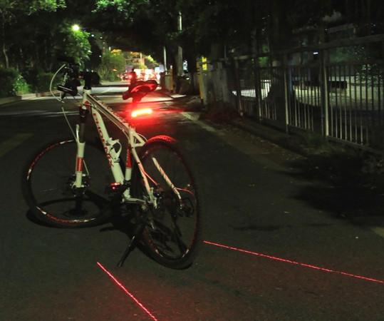 Światło tylne, dodatkowo z laserem nie jest przepisowe, jednak jest zgodne z duchem rozporządzeń, gdyż podwyższa widocznośćroweru w sposób zgodny z ogólnie przyjętąw ruchu drogowym konwencją, że co czerwone, to z tyłu. Laser świeci na jezdnię, a nie na innych i świeci z tyłu roweru. Jeśli nie ma nas na drodze mało, widoczność jest słaba lub poruszamy sięwspólnie z samochodami na jezdni, to zdaniem autora warto takie rozwiązanie wziąć pod uwagę jako opcję.   Lampka na zdjęciu to Meilan X5, którą autor testuje od roku, dostępny w sklepach w cenie od ok.125 zł.