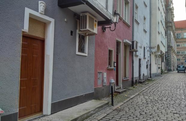 Poszerzenie otworu drzwiowego w kamienicy przy Długim Pobrzeżu jest bardzo widoczne, gdyż narusza ozdobny obrys dawnych drzwi. Nad drzwiami widoczny maszkaron przedstawiający właściciela budynku.