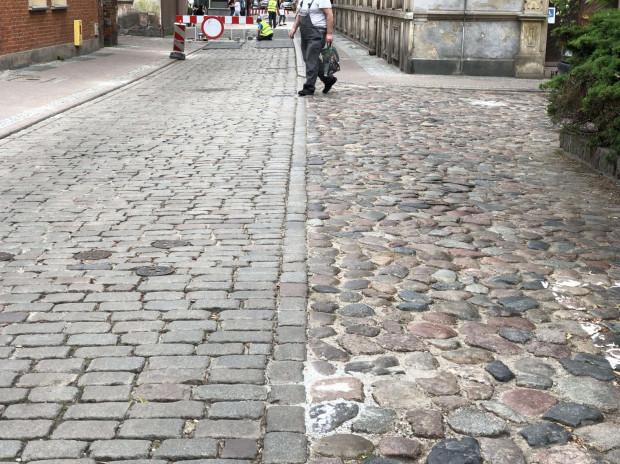 """Po prawej kamienie polne (często mówi sięna nie """"kocie łby""""), po lewej kostka kamienna nieszlifowana. Mimo, że po lewej jest jużtrochęlepiej, to do porządnej nawierzchni jednemu i drugiemu wariantowi bardzo daleko. ul. Pocztowa, niedaleko ul. Długiej."""