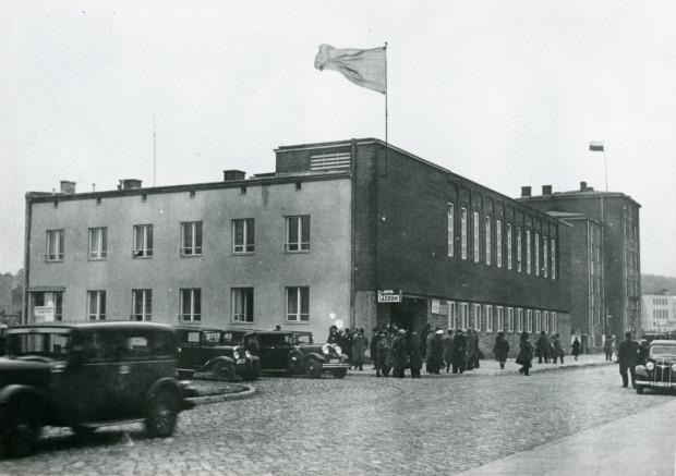 Otwarcie Domu Szwedzkiego Marynarza w Gdyni. Choć był to czerwiec, to wyjątkowo zimny, pochmurny i deszczowy - stąd też uczestnicy uroczystości stawili się na nią w prochowcach i kapeluszach.