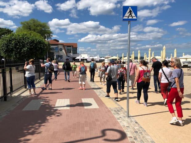 Typowa dla tego odcinka scena. Turyści nie wiedzieli, że znajdująsięna środku drogi rowerowej. Potrzeba oznakowania poziomego i lepszej separacji przestrzeni pieszej od rowerowej. Sugerujemy, żeby pasek kostki brukowej był wypukły, alternatywnie może sprawdziłby sięniski żywopłot?