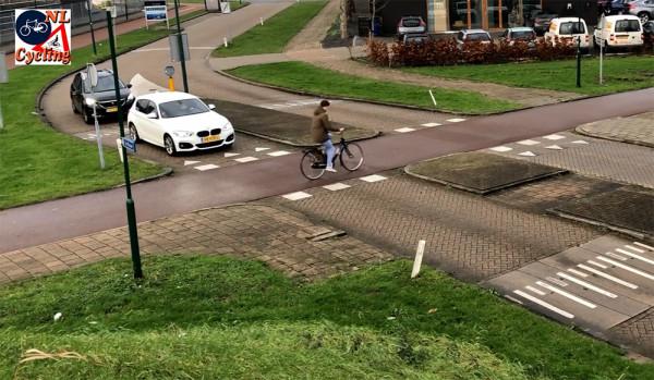Holenderskie miasto Houten - Skrzyżowanie z priorytetem dla rowerzystów. Tu widać, kto ma pierwszeństwo. Ciągłośćnawierzchni zachowuje droga rowerowa. Ulica samochodowa ma nawierzchnię z cegły. Do tego dochodzi oznakowanie pionowe i poziome oraz próg spowalniający auta. Większośćużytkowników skrzyżowania to lokalni mieszkańcy, wiedzący, że poruszanie siępieszo i rowerem jest i ma być uprzywilejowane.