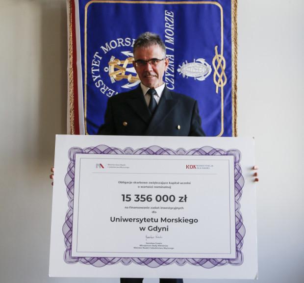 Rektor UMG prof. Janusz Zarębski z symbolicznym czekiem na obligacje skarbowe dla uczelni.