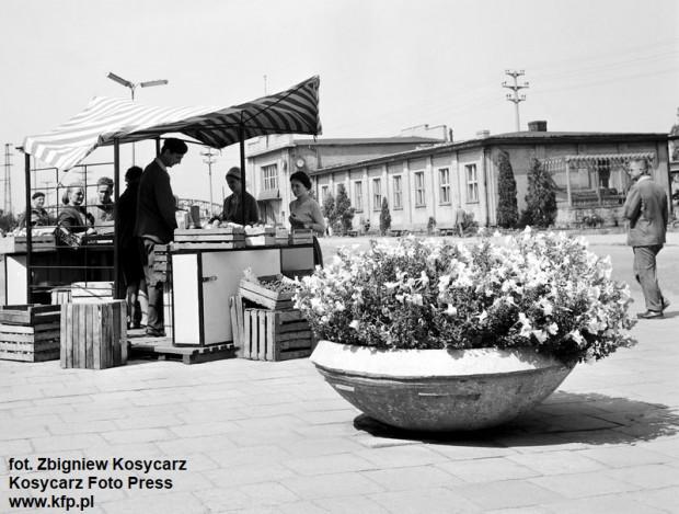Stragan z owocami i warzywami przy ul. Romana Dmowskiego (wówczas ul. Juliana Marchlewskiego), w tle budynek dworca z 1952 roku, zdjęcie wykonane w 1964 roku.
