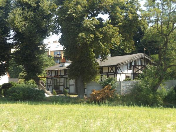 Zabytkowy dom szachulcowy na Suchaninie z przełomu XIX i XX wieku stojący między blokami.