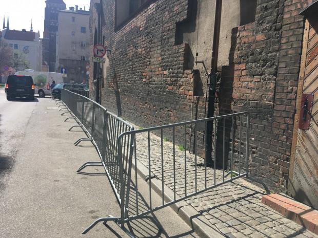 W trosce o bezpieczeństwo pieszych, wygrodzono przestrzeń przy ścianie, z której mogą się osypywać elementy elewacji.