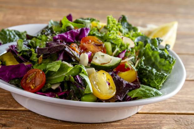 Duża porcja świeżej sałaty z oliwnym dressingiem i ziołami to świetny pomysł na zniwelowanie szkodliwości grillowania.