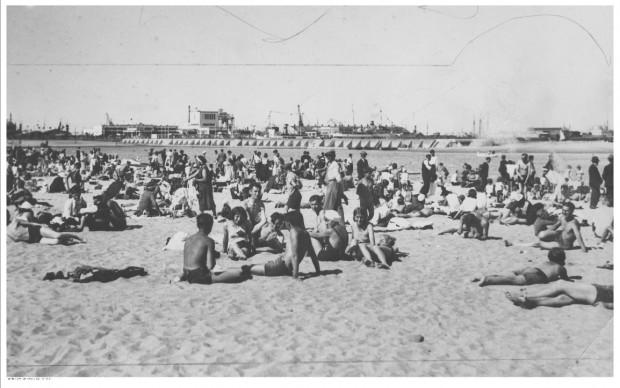 Plażowicze podczas wypoczynku na plaży w Gdyni, w tle port