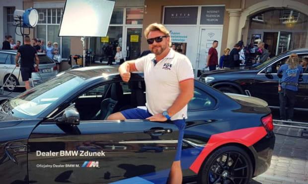 Michał Milowicz jest jednym z reżyserów nowej produkcji. Na zdjęciu pozuje przy BMW M2.