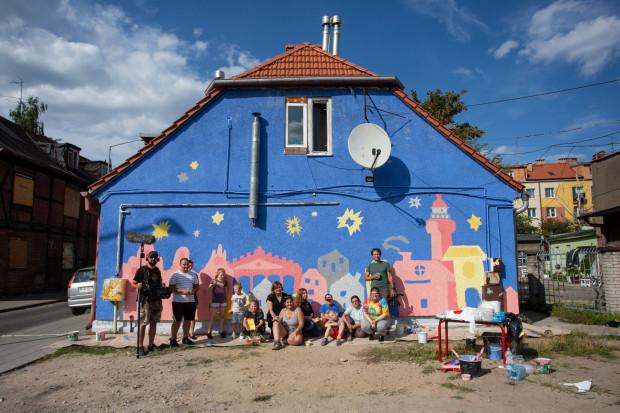 Mali artyści z Dużego i Małego Domu na Skraju pozują ze swoimi opiekunami na tle swojego dzieła.