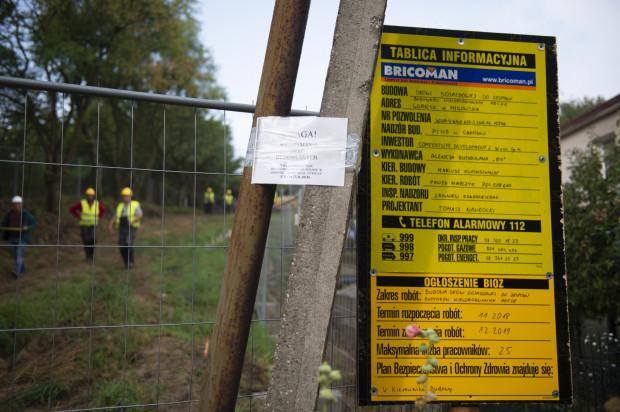 Tablica informacyjna, która zawisła na ogrodzeniu spornej nieruchomości.