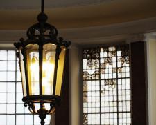 Oryginalny żyrandol w holu głównym. W tle resztki okiennego witrażu.