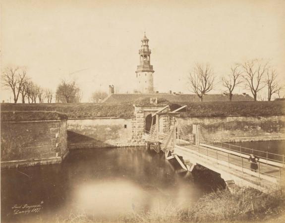 Jedno z niewielu zachowanych zdjęć, na których utrwalono barokowy hełm wieży Twierdzy Wisłoujście. Po jego zniszczeniu przez pożar 1889 roku został on zastąpiony prostym hełmem w formie krytego dachówką stożka.