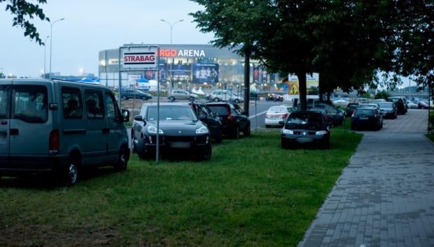 Nawet właściciele drogich aut często wolą zaparkować na trawie, niż zapłacić za parkowanie pod halą.