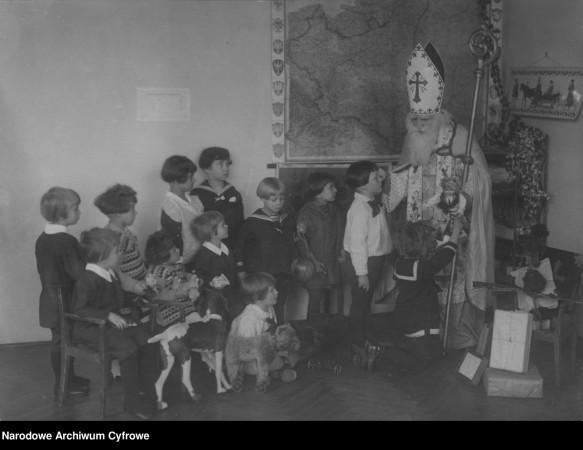 Święty Mikołaj wręczający prezenty dzieciom na gwiazdkę 1925 roku.