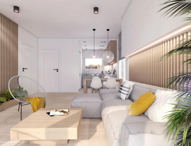 Jasny, przestronny salon z kuchnią - przykładowa aranżacja wnętrza domu na osiedlu 36 Dzielnica.
