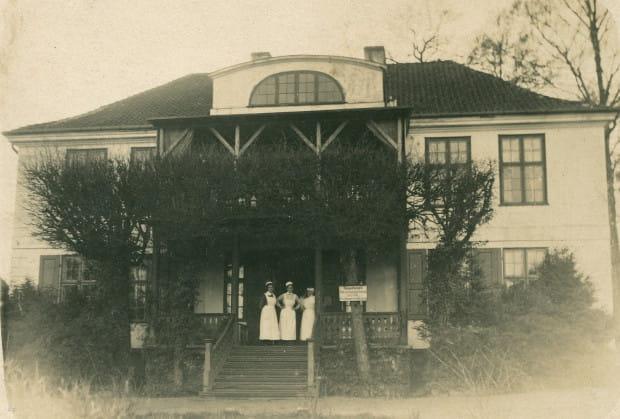 """Kolejne zdjęcie dworu z okresu I wojny światowej, a dokładnie z 1917 r. Tym razem na schodach widać postacie kobiet w strojach pielęgniarek. Fakt ulokowania w budynku lazaretu potwierdza napis na tablicy, umieszczonej na jednym z drzew obok wejścia. Niemieckie słowo """"Besuchszeit"""" oznacza po polsku dosłownie """"czas odwiedzin"""", choć bardziej trafne tłumaczenie brzmi """"godziny odwiedzin""""."""