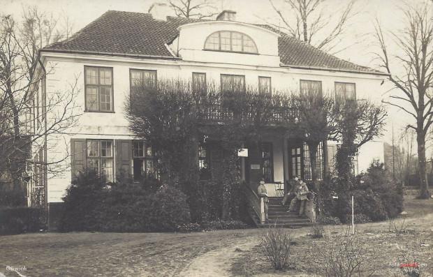 Dwór Ernsttal na zdjęciu z okresu I wojny światowej, a dokładnie z 1916 r. Budynek został wówczas zaadaptowany na lazaret, czyli polowy szpital wojskowy. Na schodach widoczni żołnierze w mundurach armii kajzerowskich Niemiec.