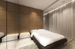 Minimalistyczne wykończenie ścian w sypialni i ograniczenie ilości mebli ma pomóc w eksponowaniu głównego mebla - łóżka w pikowanej ramie.