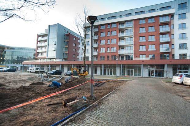 Do dawnych koszar wchodzimy przez kutą bramę od strony al. Grunwaldzkiej. Po minięciu historycznych, ale odrestaurowanych budynków, w których dziś są biura, widzimy powstający właśnie mały plac miejski. Za nim stoją pierwsze budynki mieszkalne i biurowiec (po lewej stronie).