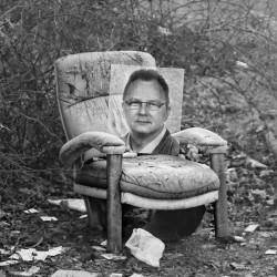 Portret autora fotografii, Grzegorza Jezierskiego, na fotelu na placu przy ul. Małomiejskiej.
